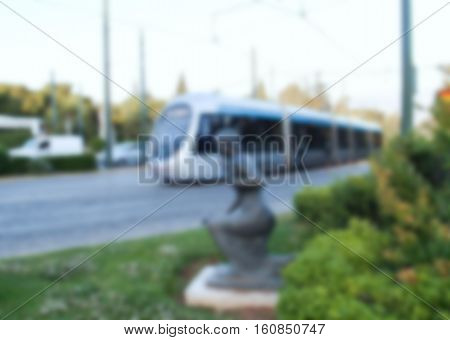 City railway transport blurry photo. European city with modern tram on street. Electrical public transport for passengers. Travel in Europe blurred image. White train on highway of modern city picture