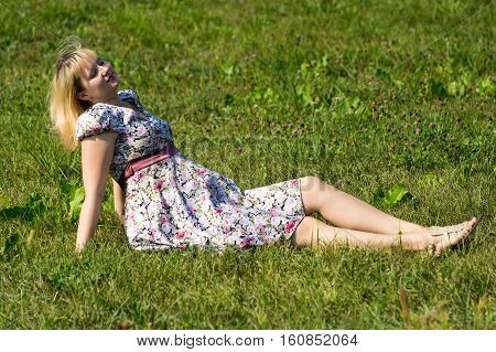 Pregnant woman sunbathing on lawn in the Park