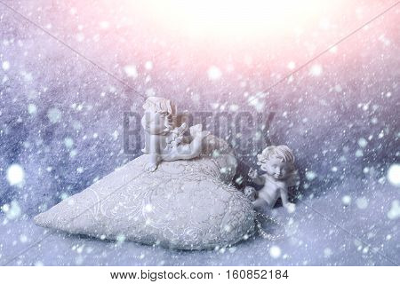 Closeup of beautiful soulful figurine composition of cupid angels for valentine day or christmas with small pillow in shape of heart lying on white wadding decorating snow horizontal picture