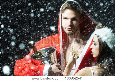 Young sexual new year couple embracing. muscular man in santa claus winter coat holding wine bottle with cork in pail in studio on black background horizontal