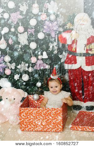 Little girl in the gift box in fron of the Christmas tree. Little cute Christmas present in the box