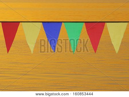 Multi Colored Triangular Flags Hanging in the Sky at an Outdoor on the background of gold water