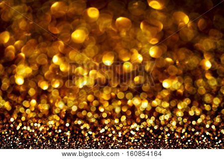Dark Gold Festive blur background. Abstract night twinkled bright background with bokeh defocused golden lights. Christmas blurry bokeh lights