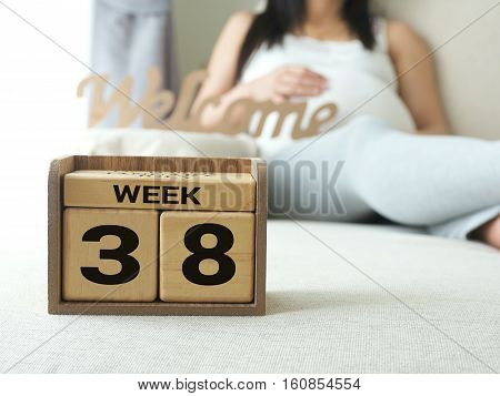 Calendar with weeks 38 of pregnant with pregnancy woman background. Maternity concept. Expecting an upcoming baby. Due date countdown.
