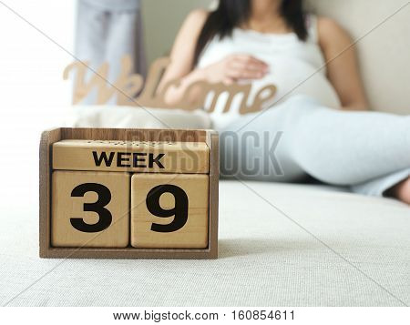 Calendar with weeks 39 of pregnant with pregnancy woman background. Maternity concept. Expecting an upcoming baby. Due date countdown.