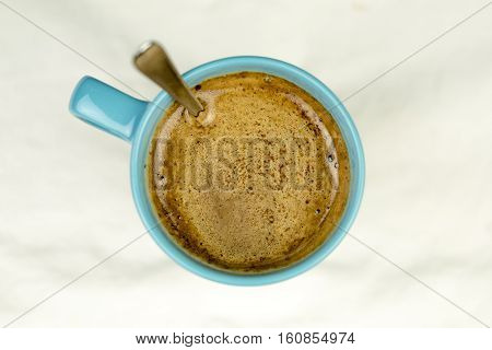 Frothy Coffee Served In Blue Mug With Silver Spoon