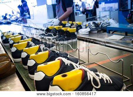 worker making shoe in production line of footwear industry