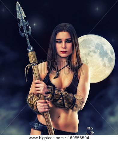 Beautiful athletic girl in the image of ancient warrior with a spear on a mystical background.