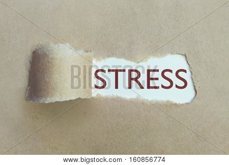 Torn paper ripped uncovering the word stress