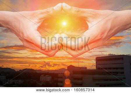 hand forming a heart shape with sunset light and copy space for add text