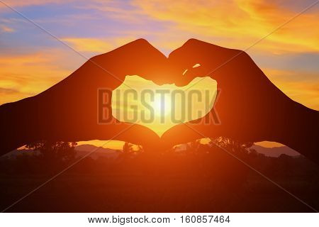 hand forming silhouette a heart shape with sunset light