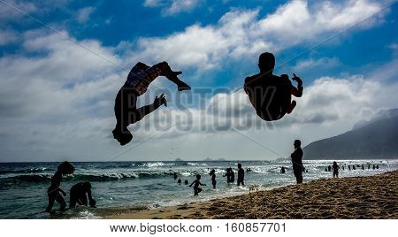 Silhouettes of two men performing somersaults at sand of Ipanema beach with silhouettes of swimming people, blue sky, white clouds and silhouettes of mountains at background, Rio de Janeiro, Brazil