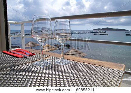 Two wine glasses on table at harbor Romantic dinner at harbor of Portofino Perfect summer vacation for couples