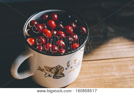 Fresh cherries in old cap on rustic wooden table.