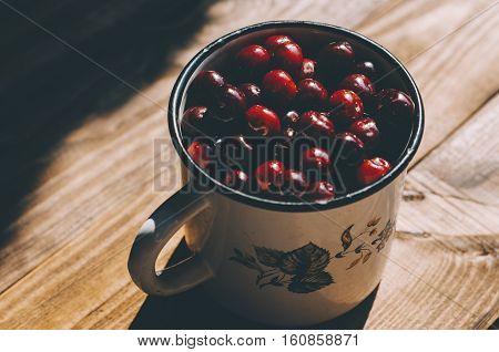 Fresh cherries in an old metal mug on rustic wooden table.