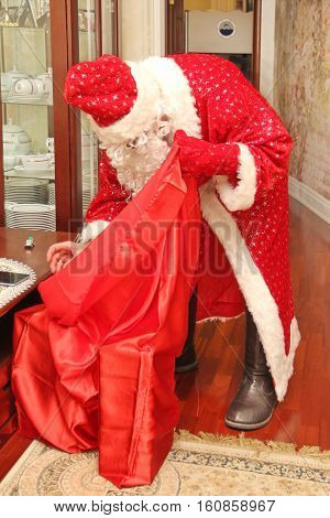 Santa Claus in a long bright suit and gloves gets gifts from the big red bag not posing natural photo