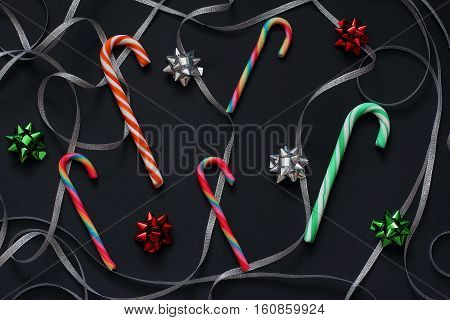 Pattern of candy cane christmas, swirls of silver ribbon and bows for gifts green, red and silver colors. Christmas/New Year decorations  Black background, top view, flat lay