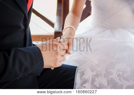 young people holding hands while sitting on a bench in the park, wedding