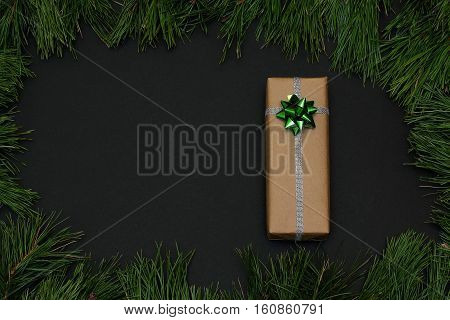 Frame of pine branches. Gift wrapped in kraft paper, decorated with ribbon silver and bow green. Christmas/New Year decorations Black background, top view, flat lay, copy space