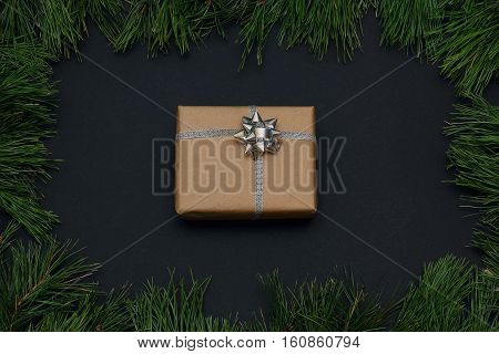 Frame of pine branches. Gift wrapped in kraft paper, decorated with ribbon and bow in silver color. Christmas/New Year decorations Black background, top view, flat lay, copy space