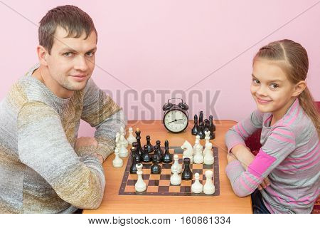 Dad And Daughter Playing Chess With A Smile And Looked Into The Frame