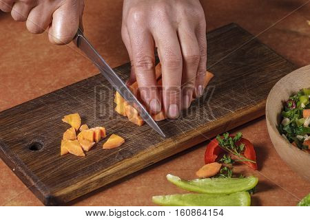Chef chopping vegetables on kitchen board. Preparing canned