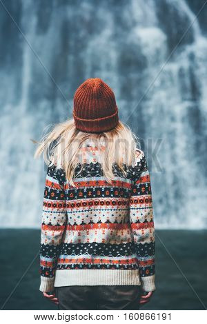 Woman enjoying waterfall Travel Lifestyle adventure concept vacations into the wild wearing cozy sweater and hat