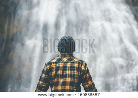Man enjoying waterfall Travel Lifestyle adventure concept vacations into the wild wearing cozy shirt and hat
