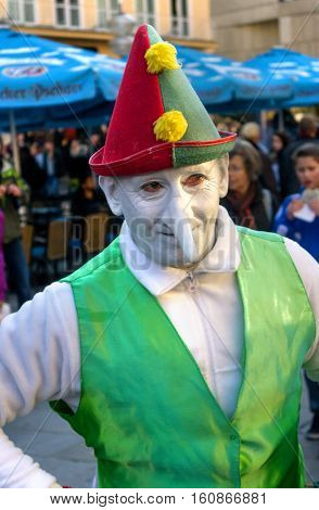 Munich, Germany - October 16, 2011: Street mime actor at Marienplatz in Munich, earns money as a clown-dwarf. The actor welcomes the audience.