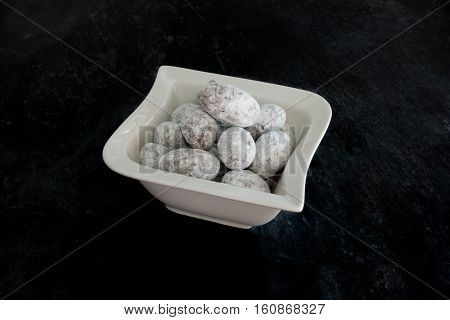 Closeup of almonds coated with chocolate and icing sugar in small white porcelain bowl on black background. Selective focus.