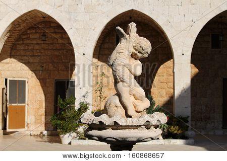 Statue of a little boy holding a beast.