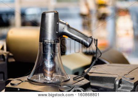 Black bullhorn public address megaphone on a loudspeaker in a blurry background