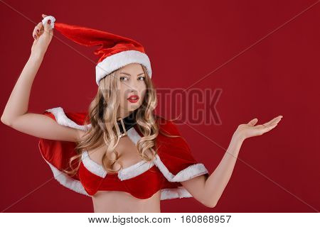 portrait of sexy woman blonde in the clothes of Santa Claus on a red background.
