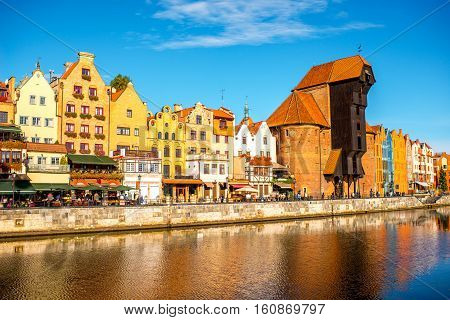 Morning view on the riverside of Motlawa river with beautiful buildings and famous historic gate of the old town in Gdansk, Poland