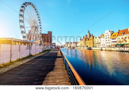 Morning view on the riverside of Motlawa river with beautiful buildings and viepoint wheel in the old town of Gdansk, Poland