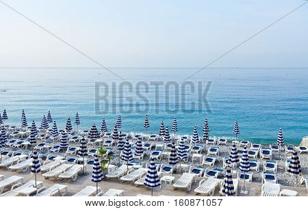 Nice stone beach and turquiose calm water of cote dAzur at summer morning, France