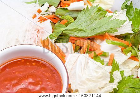 an bowl whit noodles vegetables carrots cabbage Chinese cabbage celery spicy sauce