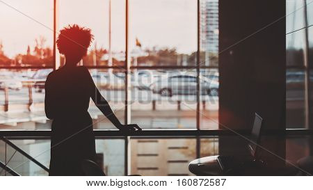 Silhouette of young black curly Brazilian girl in front of window standing in office with computer right to her blurred cityscape out of the window Rio de Janeiro Brazil