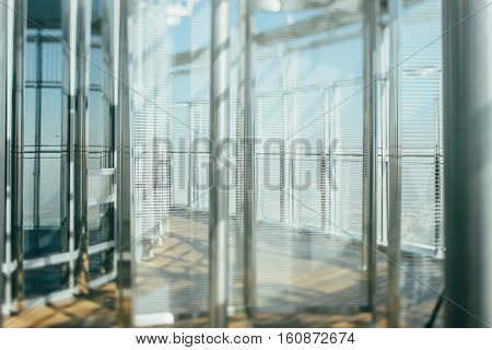 Abstract office interior background the sun rays glass steel columns and blinds view from skyscraper through the window the Dubai cityscape outside