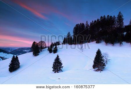 dramatic sunrise over snowy mountains Todtnauberg Germany