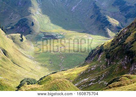 wild alpine lake between mountains in Alps