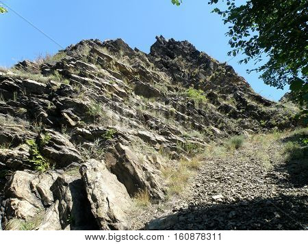 High steep mountain is composed of many rocks.