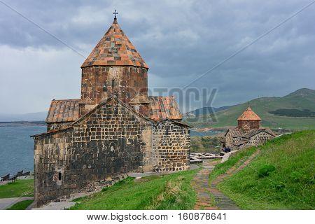 The tourists visit Sevanavank Monastery located on Sevan Peninsula among the bright green hills