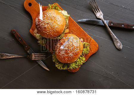 Two mouth-watering delicious homemade burger used to chop beef. on the wooden table.