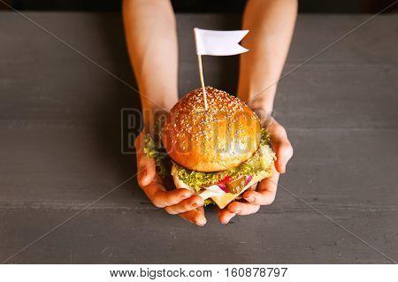 Women's hands with tasty big homemade burger.