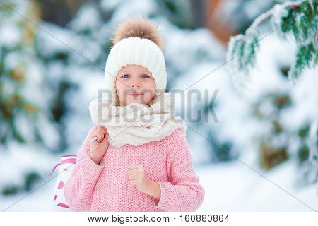 Cute little kid girl is going skate outdoors.
