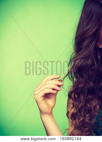 Haircare concept. Closeup part of woman head girl with long curly brown hair vivid color green background