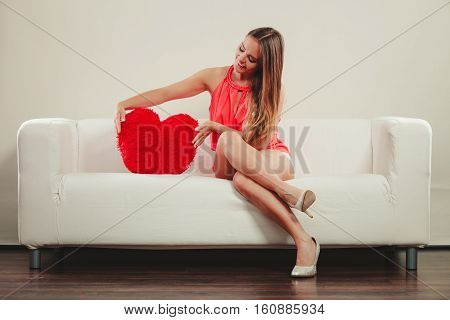 Smiling pretty cute young woman girl with red heart shape pillow sitting on white sofa couch. Valentines day love.