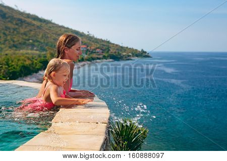 Happy family. Mother with baby swim with fun in outdoor infinity pool relax at poolside look at sea beach. Healthy lifestyle active parent people recreational activity on summer holiday with child