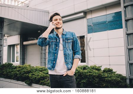 Young Man Standing Outdoors, Talking On The Phone.